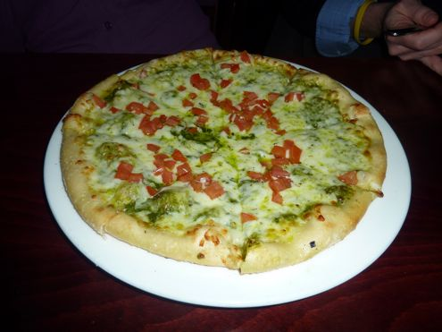 Pizza with pesto sauce, cheese, and tomatoes