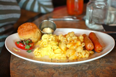 Eggs with mac and cheese, chicken sausage, and biscuit.