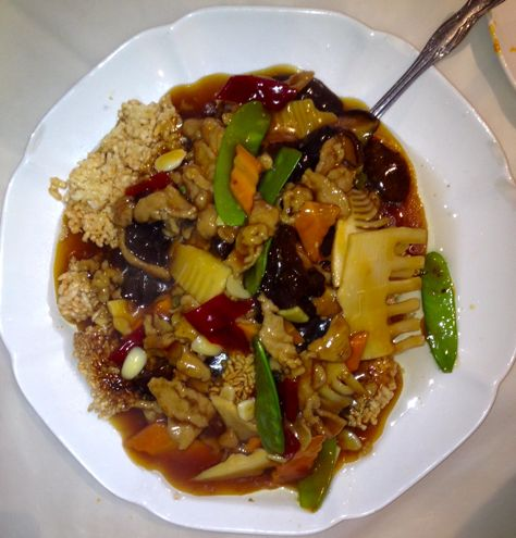 Pork and crispy rice cake in a sweet and sour sauce with vegetables